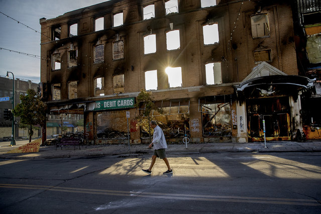 A man walks past a damaged building following overnight protests over the death of George Floyd, Sunday, May 31, 2020, in Minneapolis, Minn.  Protests were held throughout the country over the death of Floyd, a black man who died after being restrained by Minneapolis police officers on May 25.  (Photo by Elizabeth Flores/Star Tribune via AP Photo)