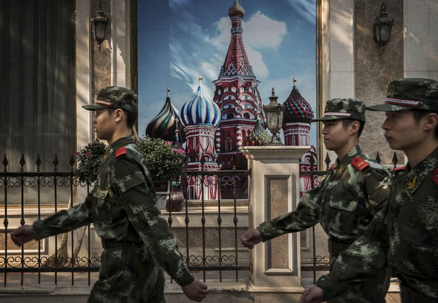 Chinese paramilitary soldiers march passed a mural showing St. Peter's Basilica in Moscow's Red Square outside a Russian restaurant on September 5, 2014 in Beijing, China. Russia and China are traditional allies in global politics. (Photo by Kevin Frayer/Getty Images)