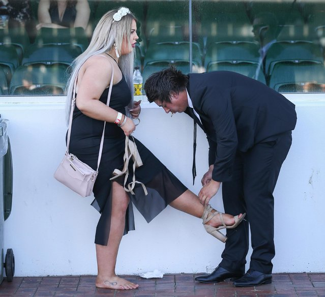 A man helps his female companion with her shoe on 2017 Derby Day at Flemington Racecourse on November 4, 2017 in Melbourne, Australia. (Photo by Splash News and Pictures)
