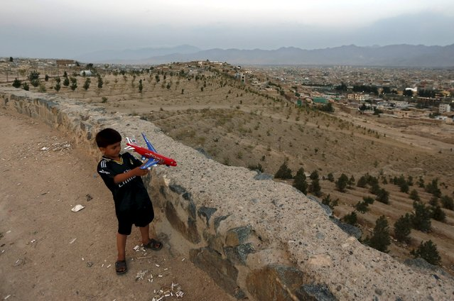 A boy plays with a toy airplane on a hilltop Kabul, Afghanistan August 24, 2015. (Photo by Mohammad Ismail/Reuters)
