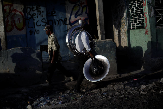 A man walks carrying a sousaphone in a street of Port-au-Prince, Haiti, July 15, 2016. (Photo by Andres Martinez Casares/Reuters)