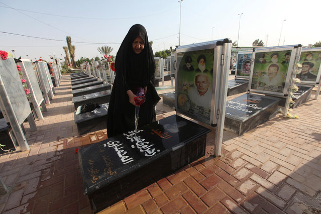 """A woman washes the grave of her relative at the Wadi al-Salam cemetery, Arabic for """"Peace Valley"""", in Najaf, south of Baghdad, Iraq, August 5, 2016. (Photo by Alaa Al-Marjani/Reuters)"""