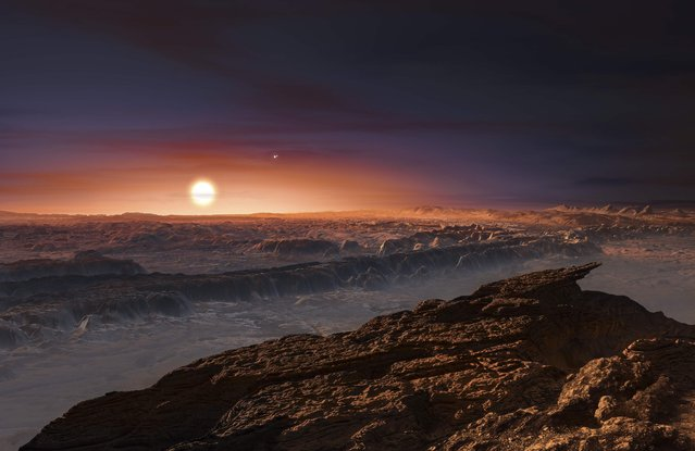 """A view of the surface of the planet Proxima b orbiting the red dwarf star Proxima Centauri, the closest star to our Solar System, is seen in an undated artist's impression released by the European Southern Observatory August 24, 2016. Scientists Wednesday announced the discovery of an Earth-sized planet orbiting the star nearest our Sun, opening up the glittering prospect of a habitable world that may one day be explored by robots. Named Proxima b, the planet is in a """"temperate"""" zone compatible with the presence of liquid water – a key ingredient for life. Proxima b is a mere four light years from the solar system, meaning that it is essentially in our backyard on the scale of our galaxy, the Milky Way. It has a mass around 1.3 times that of Earth, and orbits about 7 million km (4.35 million miles) from its star. (Photo by M. Kornmesser/Reuters/ESO)"""