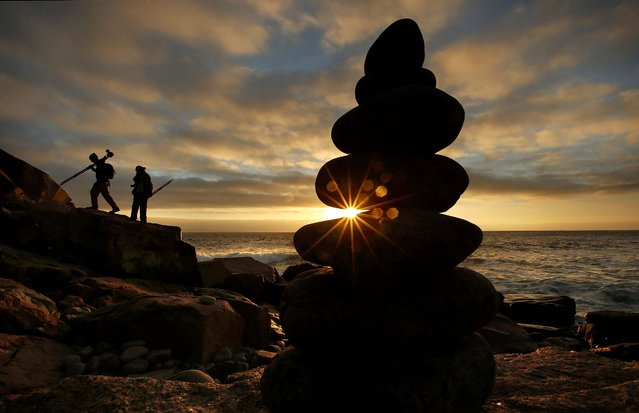 Professional photo guide Vincent Lawrence of Seal Harbor, Maine, left, and his client Frank Gallagher, of Silver Spring, Md., move to a new position while photographing the rocky coast of Maine's Acadia National Park at dawn, Friday, October 3, 2014. A 15-inch-high rock cairn stands in the foreground. (Photo by Robert F. Bukaty/AP Photo)
