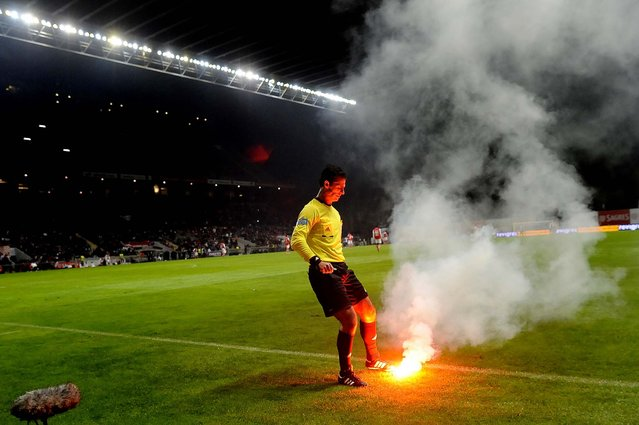 Referee Carlos Xistra tries to extinguish a flare thrown by FC Porto's fans at the game with Sporting Braga during their Portuguese League soccer match at the Municipal Stadium in Braga, November 25, 2012, Portugal. Porto won 2–0. (Photo by Paulo Duarte/Associated Press)