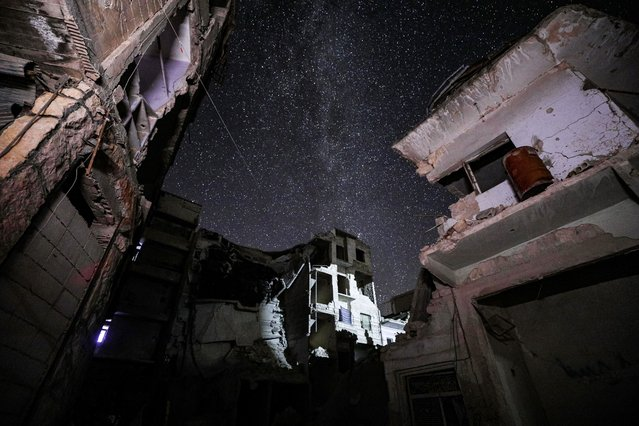This long-exposure picture taken early on June 27, 2020 shows a view of buildings destroyed by prior bombardment in the town of Ariha in Syria's rebel-held northwestern Idlib province, as the Milky Way galaxy is seen in the night sky above. (Photo by Omar Haj Kadour/AFP Photo)