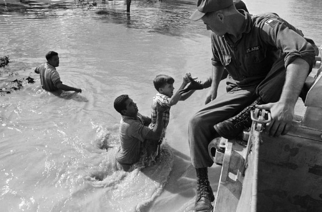 Ricky Knight, 13, is pulled from the floodwaters in the Parkwood Addition of Harlingen, flooded by the overflowing Arroyo Colorado in Harlingen on September 25, 1967. (Photo by Ted Powers/AP Photo)