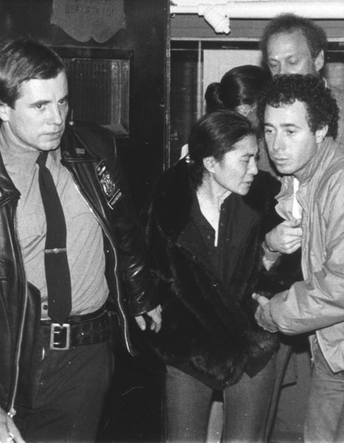 Yoko Ono, center, is aided by a policeman and David Geffen, right, of Geffen Records as she leaves Roosevelt Hospital in New York late Monday night, December 8, 1980 after the death of her husband John Lennon.  Lennon was shot outside his apartment in New York after returning from the recording studio. (Photo by Lyndon Fox/AP Photo)