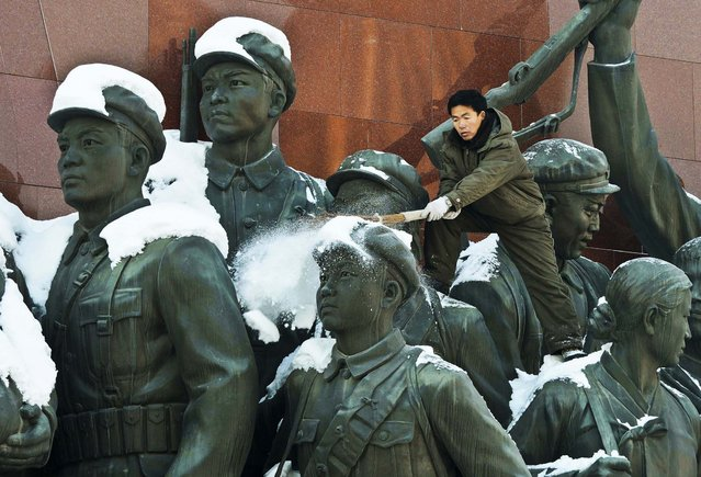 A man brushes snow from the monument of anti-Japanese revolutionary fighters on Mansu Hill in Pyongyang, North Korea, December 10, 2012. (Photo by Kyodo News)