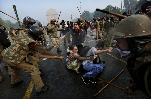 Protesters shield themselves as police beat them with sticks during a violent demonstration near the India Gate against a gang rape and brutal beating of a 23-year-old student on a bus last week, in New Delhi, India, December 23, 2012. The attack last Sunday has sparked days of protests across the country. (Photo by Kevin Frayer/Associated Press)