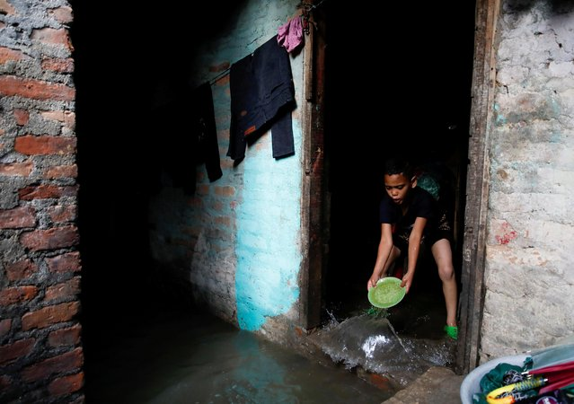 A boy uses a plate to clear water entering his house as the river overflows due to incessant rainfall at a slum along the bank of Bagmati River in Kathmandu, Nepal on July 20, 2020. (Photo by Navesh Chitrakar/Reuters)