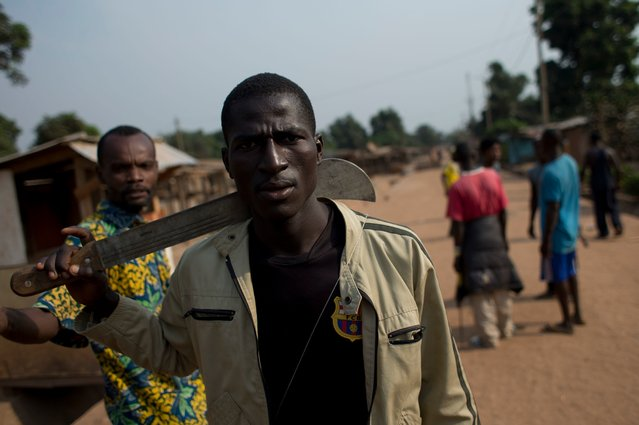 A member of an armed neighborhood defense squad, which residents say is not anti-balaka, but local Christian residents protecting themselves, carries a machete as he walks near a roadblock in Bangui, Central African Republic, Tuesday, December 31, 2013. (Photo by Rebecca Blackwell/AP Photo)