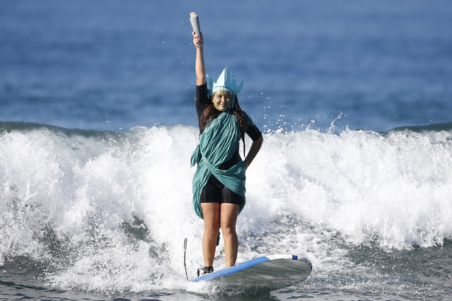 Colby Palacio, 14, rides a wave dressed as the Statue of Liberty during the 7th annual ZJ Boarding House Haunted Heats Halloween surf contest. (Photo by Lucy Nicholson/Reuters)
