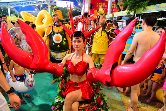 A performer dressed as a lobster is seen during a lobster-themed electronic music party at a water park on August 01, 2020 in Hangzhou, Zhejiang Province of China. (Photo by Lian Guoqing/VCG via Getty Images)