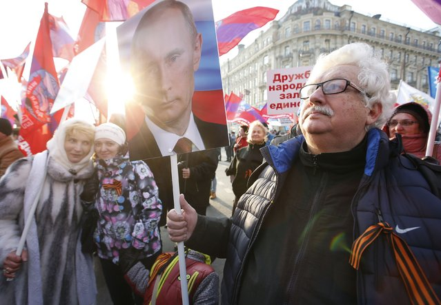 A man carries a portrait of Russia's President Vladimir Putin as he attends a demonstration on National Unity Day in Moscow November 4, 2014. (Photo by Sergei Karpukhin/Reuters)