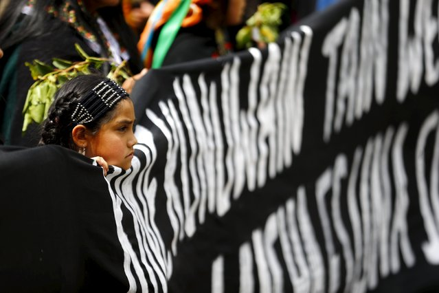 An Indigenous Mapuche girl holds a banner during a protest march by Mapuche Indian activists against Columbus Day in downtown Santiago, Chile, October 12, 2015. (Photo by Ivan Alvarado/Reuters)
