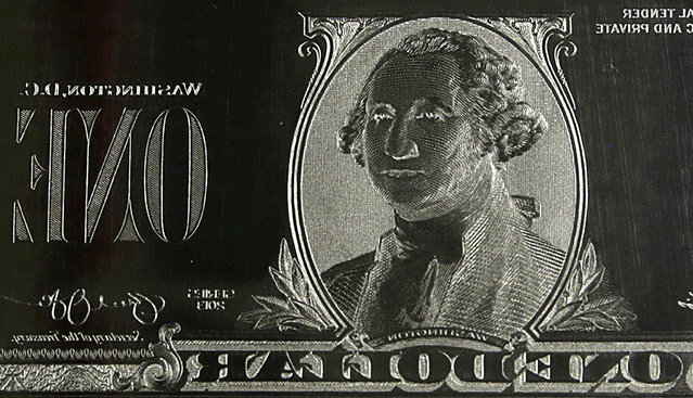 The image of President George Washington is seen on an engraving plate for a one dollar bill at the Bureau of Engraving and Printing in Washington November 14, 2014. (Photo by Gary Cameron/Reuters)