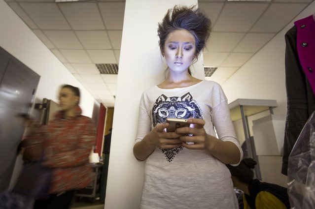 A model checks her mobile phone backstage during Kazakhstan Fashion Week in Almaty, Kazakhstan, October 14, 2015. (Photo by Shamil Zhumatov/Reuters)