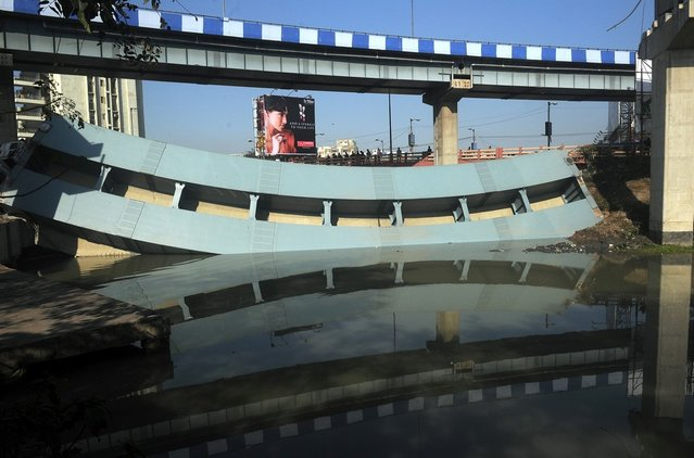 Indian nlookers stand near the collapsed portion of a flyover in Kolkata on March 3, 2013. A huge portion of a flyover on the eastern side of the Indian metropolis collapsed leaving three persons injured, the flyover connects the airport with Eastern Metropolitan Bypass and the eastern and southern suburbs.   As the debris fell into a canal running below the flyover, it took down a truck the driver and two others were rescued from the canal by fire-brigade personnel and locals. (Photo by Dibyangshu Sarkar/AFP Photo)