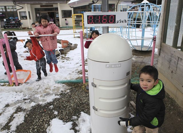 Kindergarten children play near a geiger counter, measuring a radiation level of 0.160 microsievert per hour, about 50 kilometers from the crippled Fukushima Daiichi nuclear power plant, in Nihonmatsu, Fukushima Prefecture, Japan, on March 4, 2013. (Photo by Chris Meyers /Reuters)