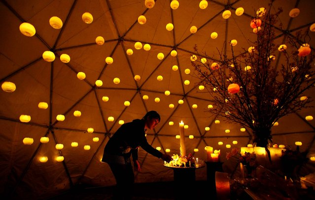 A woman lights candles to pay tribute to the victims of the March 11, 2010 earthquake and tsunami at a make-shift altar in a park in Tokyo. (Photo by Junji Kurokawa/Associated Press)