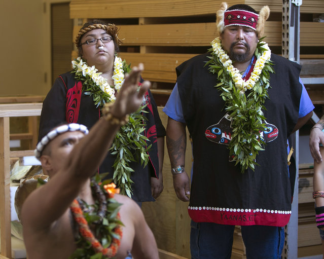 Tlingit Tribal members from Klawock, Alaska Eva Rowan, center, and Jonathan Rowan, right, watch Okolani Tallett perform a hula dance at the Honolulu Museum of Arts, Thursday, October 22, 2015, in Honolulu.   A totem pole, stolen by actor John Barrymore during a sailing trip to Alaska in 1931, was returned to the Tribe today by the Honolulu Museum of Arts where it was on display since the early 1980s. The totem pole was carved by the ancestors of the Tlingit Tribe. (Photo by Marco Garcia/AP Photo)