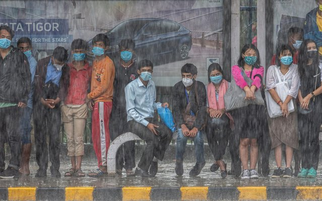 People wait at a bus stop during heavy rain in Kathmandu, Nepal on September 21, 2020. The government eased the coronavirus lockdown for economic activities despite the number of COVID-19 cases is on the rise in Nepal. (Photo by Narendra Shrestha/EPA/EFE/Rex Features/Shutterstock)