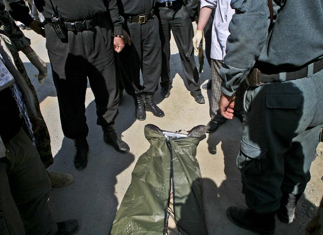 Afghan Police officers stand around a dead body after U.S. forces fired on an Afghan truck, killing two passengers and injuring another on the road between Kabul and Bagram, Afghanistan, on March 11, 2013. (Photo by Ali Hamed Haghdoust/Associated Press)