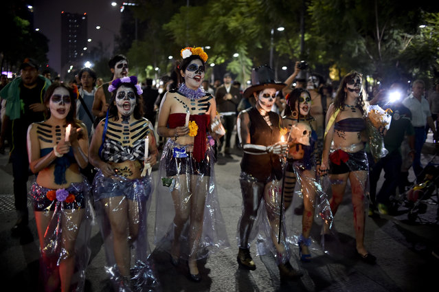 "Women painted as ""Catrina"" take part in the Procession of the Catrinas along Reforma Avenue in Mexico City on October 25, 2015. Catrina is a cartoon character created by cartoonist Jose Guadalupe Posada and baptized by artist Diego Rivera, who popularized it and whose character is now part of Mexican culture during the celebrations of the Day of the Dead. (Photo by Yuri Cortez/AFP Photo)"