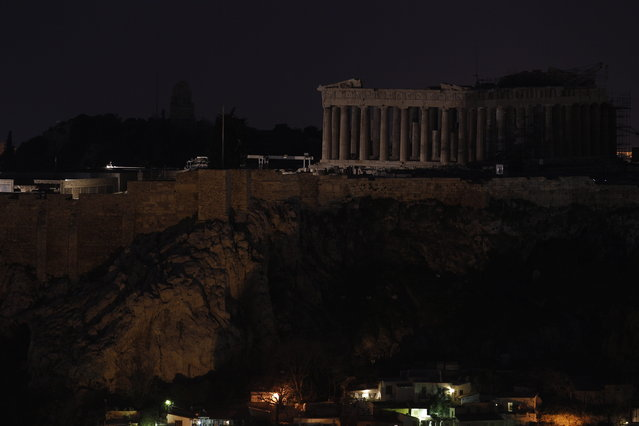 The Parthenon temple stands atop the Acropolis hill after turning off the lights to mark the annual Earth Hour in Athens, on Saturday March 23, 2013. In Greece, floodlights in several monuments and public buildings were switched off for one hour at 8:30 p.m. local time. Thousands of businesses and municipalities also dimmed their lights. (Photo by Kostas Tsironis/AP Photo)