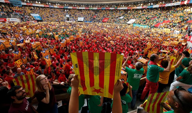 """People display """"Esteladas"""" (Catalan separatist flags) during a biannual competition where people form human towers called """"castell"""" during a biannual competition in Tarragona city, Spain, October 2, 2016. (Photo by Albert Gea/Reuters)"""