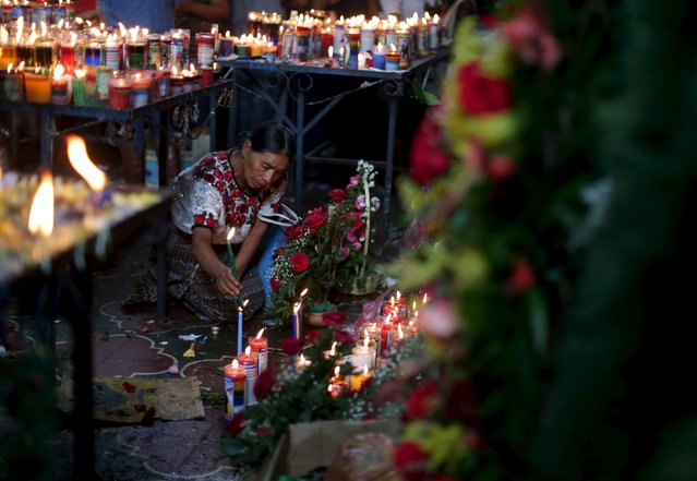 A woman lights candles in the church in honor of San Simon in Iztapa, in Chimaltenango, around 62 km (39 miles), from Guatemala City, October 28, 2015. (Photo by Jorge Dan Lopez/Reuters)