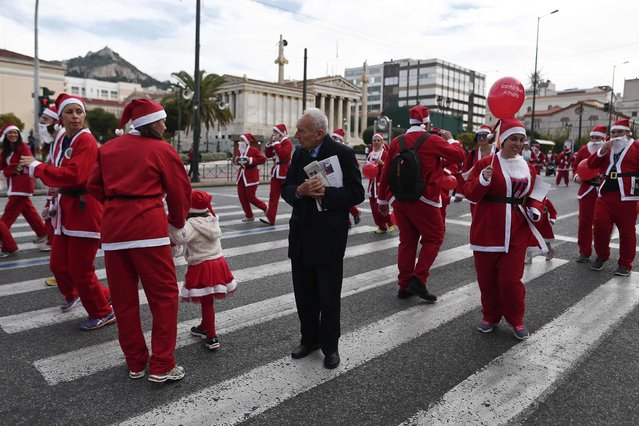A man stands among people dressed in Santa costumes taking part in the Santa Claus Run in Athens December 7, 2014. (Photo by Alkis Konstantinidis/Reuters)