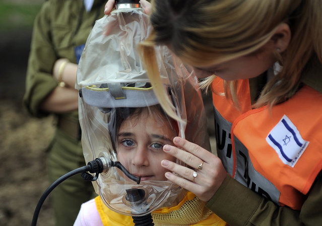 An Israeli soldier instructs children on how to wear a gas mask during an emergency drill simulating a rocket attack in the central town of Kiryat Malachi, on February 14, 2013. (Photo by David Buimovitch/AFP Photo /The Atlantic)