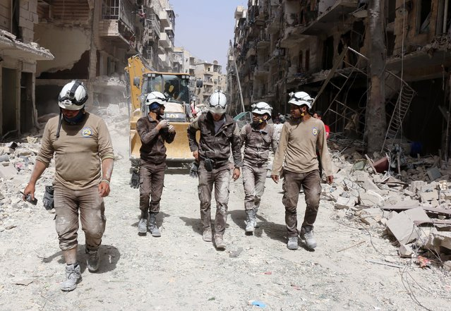 Syrian civil defence volunteers, known as the White Helmets, walk amidst the debris following a reported air strike by Syrian government forces in the rebel-held neighbourhood of Sukkari in the northern city of Aleppo on June 3, 2016. Regime air strikes killed dozens of civilians in the Syrian city of Aleppo and nearby areas as the UN Security Council prepared to discuss emergency aid drops to besieged areas. (Photo by Thaer Mohammed/AFP Photo)