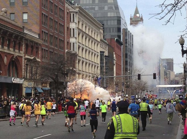Runners continue to run towards the finish line of the Boston Marathon as an explosion erupts near the finish line of the race in this photo exclusively licensed to Reuters by photographer Dan Lampariello after he took the photo in Boston, Massachusetts, April 15, 2013. (Photo by Dan Lampariello/Reuters)