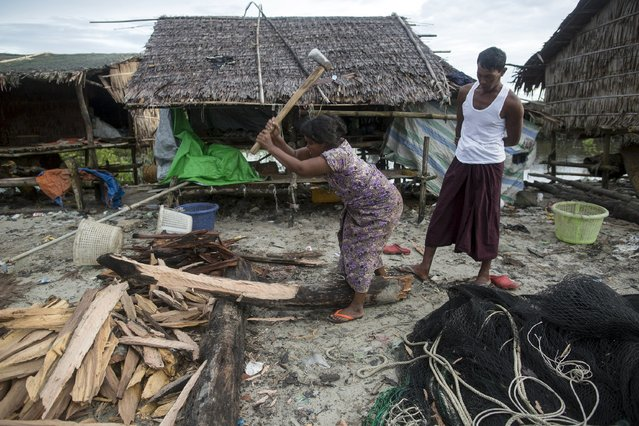 A woman chops firewood as her husband watches from behind her in Kyaukpyu township, Rakhine state, Myanmar October 6, 2015. (Photo by Soe Zeya Tun/Reuters)