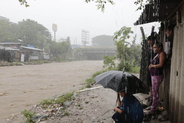 People watch the rising waters of the Rio Bermejo in the wake of Hurricane Iota in San Pedro Sula, Honduras, Tuesday, November 17, 2020. Hurricane Iota tore across Nicaragua on Tuesday, hours after roaring ashore as a Category 4 storm along almost exactly the same stretch of the Caribbean coast that was recently devastated by an equally powerful hurricane. (Photo by Delmer Martinez/AP Photo)