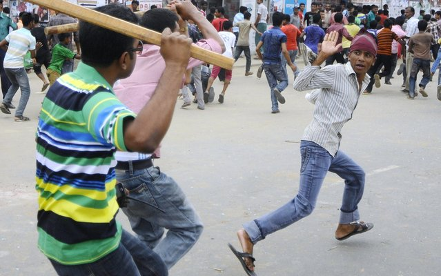 Plain-clothed Bangladeshi police brandish sticks as they attempt to break up demonstrating garment workers following the collapse of an eight-storey building, in Dhaka on April 26, 2013.  Bangladeshi police battled April 26 to control huge crowds of garment workers angrily protesting the death of more than 300 colleagues in a collapsed building as rescue efforts stretched into a third day. (Photo by AFP Photo/STR)