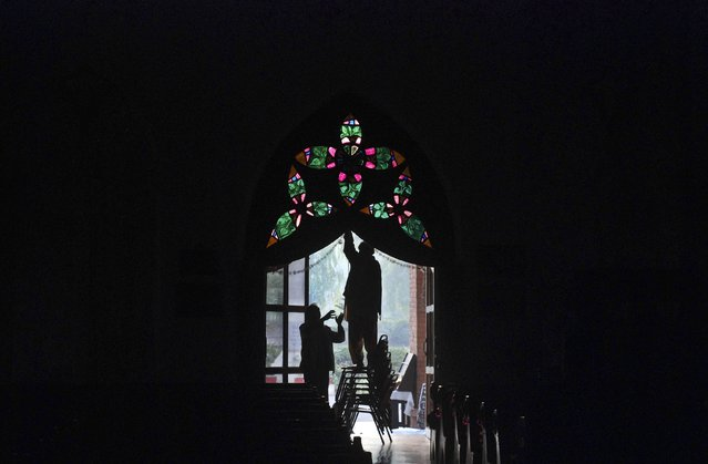 Men are silhouetted as they decorate a door at the St Johns Cathedral Church, on Christmas eve in Peshawar December 24, 2014. (Photo by Khuram Parvez/Reuters)