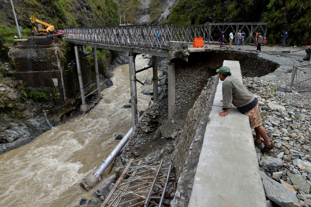 A local resident looks at a bridge damaged at the height of Typhoon Haima in Benguet province, in northern Philippines, October 21, 2016. (Photo by Ezra Acayan/Reuters)