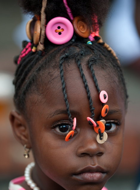 A girl presents an Afro-Colombian hairstyle during the 9th contest of Afro-hairdressers, in Cali, Valle del Cauca departament, Colombia, on May 12, 2013. The Afro hairstyles have their origins in the time of slavery, when women sat to comb their children hair after work. (Photo by Luis Robayo/AFP Photo)