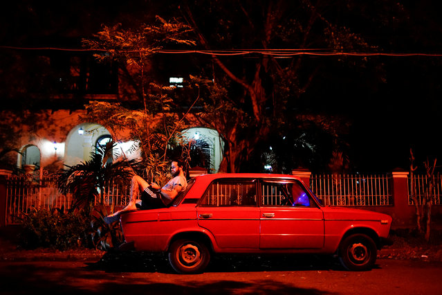 Tourist guide Daniel Hernandez, 26, sits on his Russian-made car as he speaks to his girlfriend who lives in Britain, at an internet hotspot in Havana, Cuba, September 24, 2017. (Photo by Alexandre Meneghini/Reuters)
