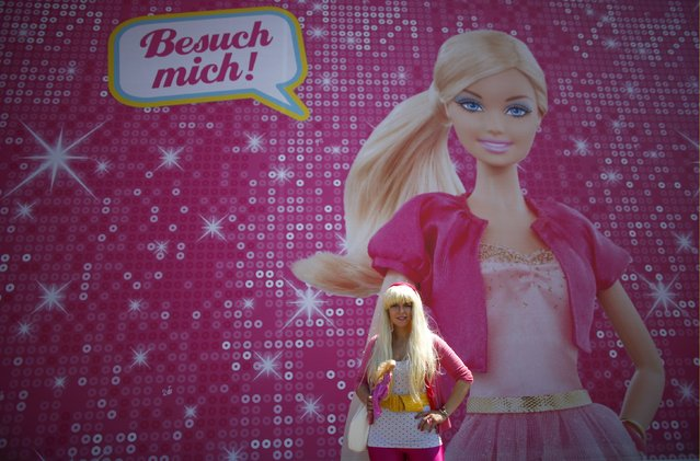 """Model Ina Blaubeer poses with a Barbie doll in front a """"Barbie Dreamhouse"""" of Mattel's Barbie dolls in Berlin, May 16, 2013. (Photo by Fabrizio Bensch/Reuters)"""