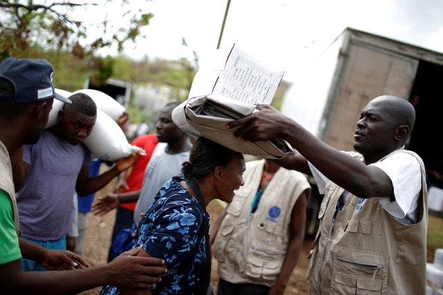 A woman is helped to carry a relief supplies kit during a distribution after Hurricane Matthew hit Jeremie, Haiti, October 19, 2016. (Photo by Carlos Garcia Rawlins/Reuters)