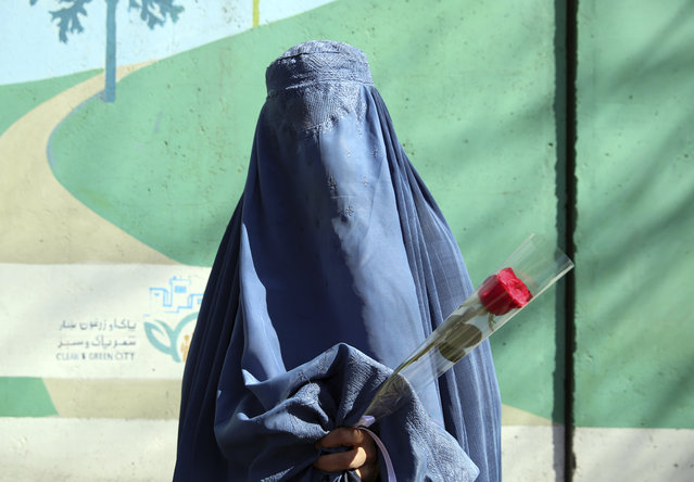 A woman holds a rose during an event marking the International Women's Day in Kabul, Afghanistan, Sunday, March 8, 2020. Afghan civil society activists gathered the less fortunate from the streets of Kabul to mark International Women's Day in Kabul. (Photo by Rahmat Gul/AP Photo)