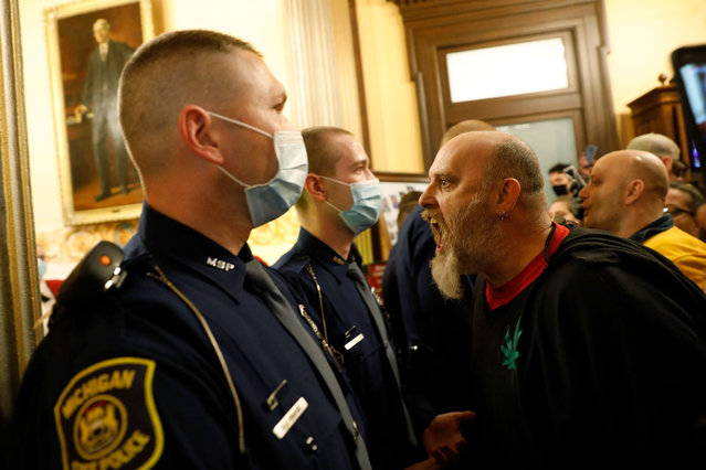 Protestors try to enter the Michigan House of Representative chamber and are being kept out by the Michigan State Police after the American Patriot Rally organized by Michigan United for Liberty protest for the reopening of businesses on the steps of the Michigan State Capitol in Lansing, Michigan on April 30, 2020. The group is upset with Michigan Gov. Gretchen Whitmer's mandatory closure to curtail Covid-19. (Photo by Jeff Kowalsky/AFP Photo)