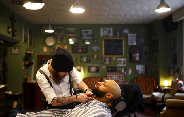 "Alex ""Torreto"" Vellios, a 26-year old barber styles the beard of his assistant Sam at his Torreto barber shop in Frankfurt January 6, 2015. (Photo by Kai Pfaffenbach/Reuters)"