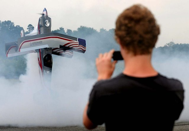 "A visitor to the Jet-Flugtage model aircraft festival takes pictures of a remote-controlled replica of the U.S. double-decker ""Ultimate Dash 300 S"" at the airport in Ganderkesee, Germany. (Photo by Ingo Wagner/AFP Photo)"
