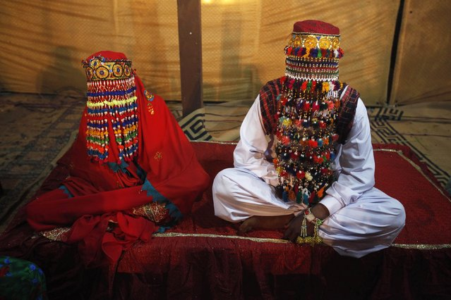 A bride and groom sit together during a mass marriage ceremony held in Karachi January 2, 2015. A total of 50 couples from the Hindu community across Pakistan took their wedding vows during the mass wedding ceremony organized by the Pakistan Hindu Council. (Photo by Athar Hussain/Reuters)